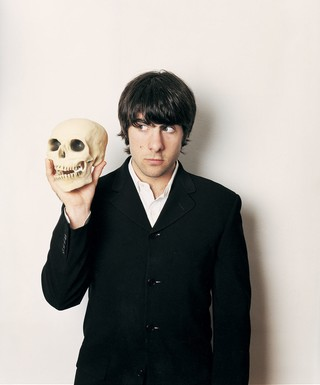 Jason Schwartzman in i-D magazine wearing a suit and holding a skull