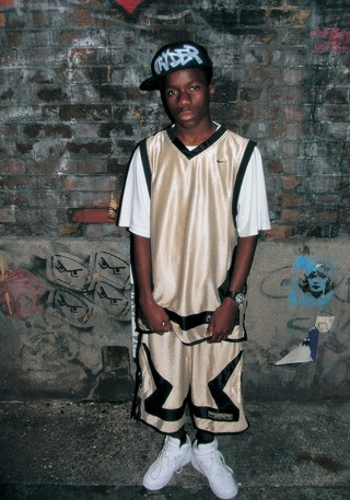 The History of Grime: Tinchy Stryder in a gold basketball shirt and shorts