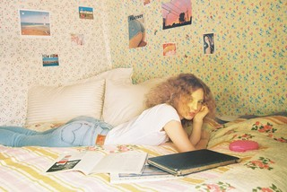Petra Collins on the bed in her bedroom